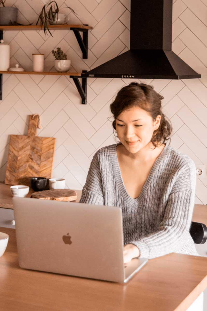 Chica en su cocina recién reformada con un ordenador