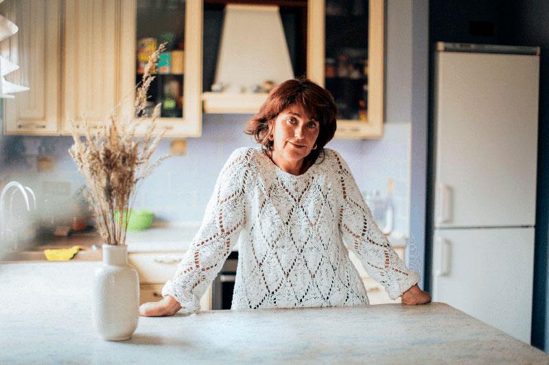 Señora en la cocina de su vivienda a la venta