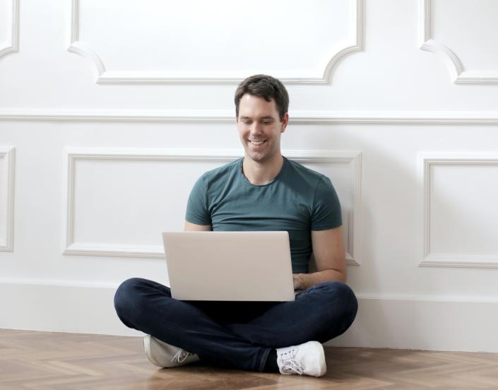 Hombre comprando casa con su computadora