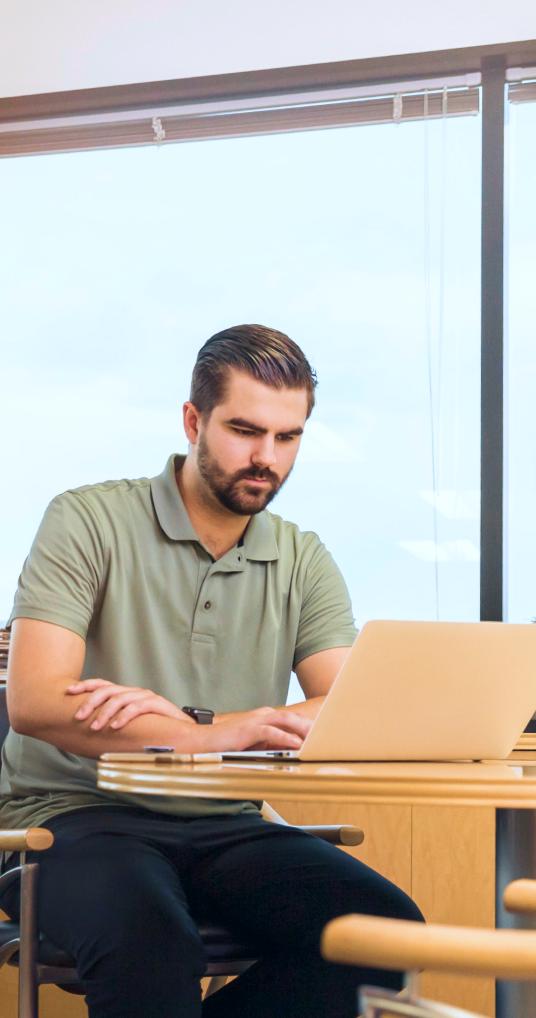 Chico con la computadora en su nuevo departamento